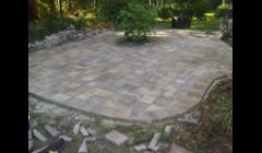 Free form paver patio with sailor course border during construction.