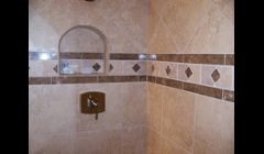 Shower done in Marazzi Tile materials and a light emperador marble border.