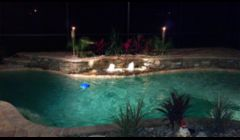 Custom Pool with natural stone and fountain. Caribben Blue Pebble Tec Finish