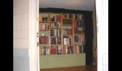 A bookcase I built that acts as a room divider --- It stands on its own. Behind it is a buffet.