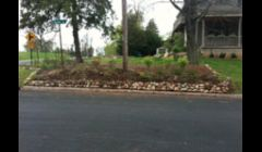 Small boulder retaining wall along street to prevent erosion and mulch from washing away